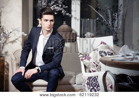 Handsome young man in a classic suit sitting on a sofa in restaurant