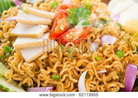 Close up Dry Instant Noodle, Malaysian style maggi goreng mamak or spicy dry curry instant noodles. Asian cuisine, ready to serve on wooden dining table setting. Fresh hot with steamed smoke.