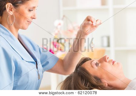 Alternative medicine therapist using pendulum to make a diagnosis