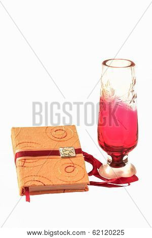romantic memo book and colored crystal vase isolated on white background