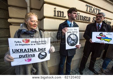 KRAKOW, POLAND - MAR 9, 2014: Unidentified participants during protest near Cracow Opera, against bringing Russian troops in the Crimea. Posters: Ukraine without Putin, and Putin - Thief.