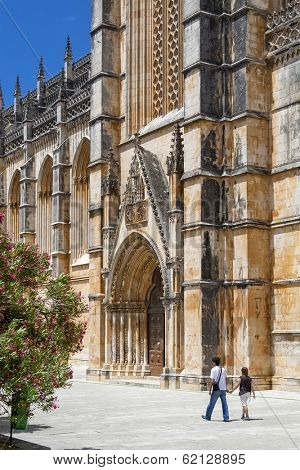 Batalha, Portugal - July 17, 2013: Locals passing by the South Portal of the Batalha Monastery. Masterpiece of the Gothic and Manueline. UNESCO World Heritage Site.