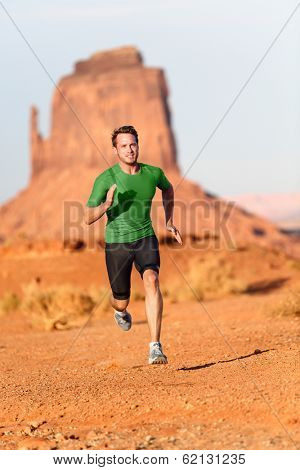 Trail running man. Male runner in Monument Valley sprinting fast training for success. Fit sports fitness model working out in amazing landscape nature. Arizona, Utah, USA.