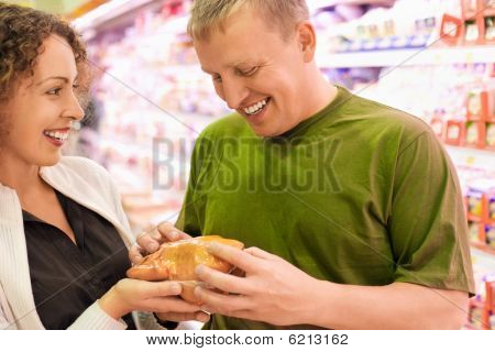 Smiling Young Man And Woman Buy Chicken In Supermarket