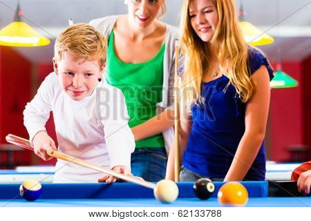 Family playing together billiard, Brother kick off with queue and balls on pool table