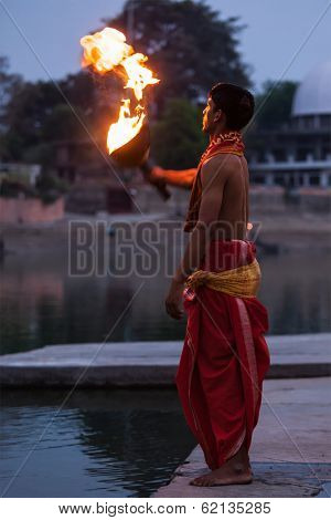 UJJAIN, INDIA - APRIL 23, 2011: Brahmin performing Aarti pooja ceremony at holy river Kshipra. Aarti is Hindu religious ritual of worship, part of puja when light is offered to one or more deities