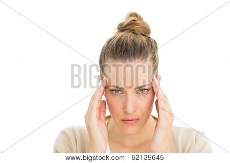 Woman with headache touching her temples looking at camera on white background