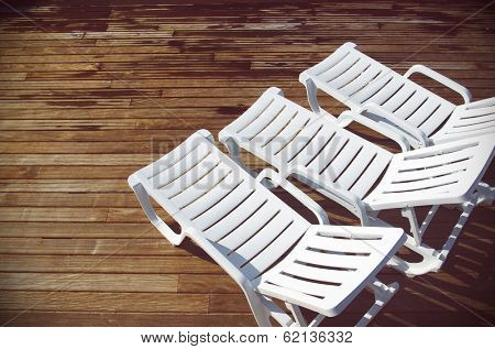 Top view of three empty white deck chairs in a swimming pool deck