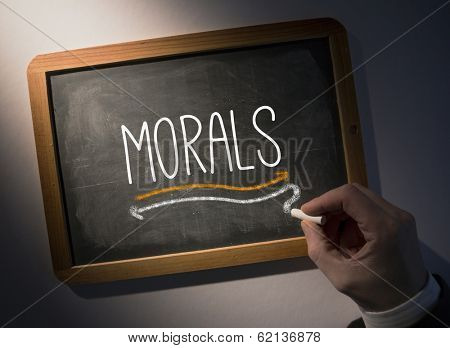 Hand writing the word morals on black chalkboard