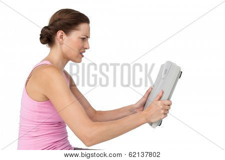 Side view of an annoyed young woman with weight scale over white background