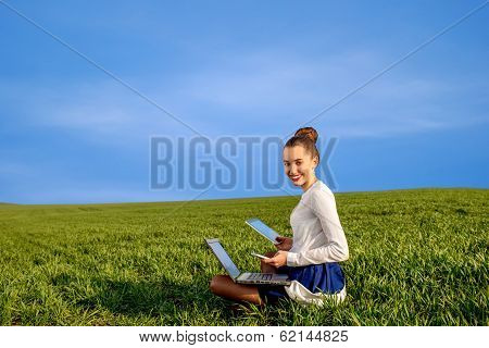 Smiling Business Woman With Laptop, Tablet And Phone Sitting On The Greenfield