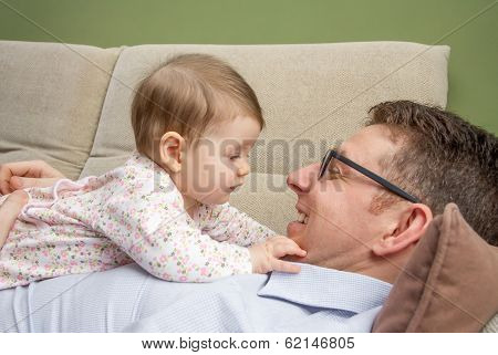 Cute baby playing with her happy father in a sofa