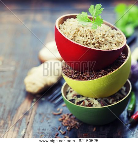 Three bowls with different types of rice on wooden background