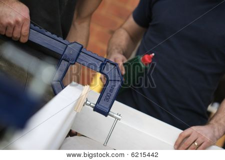Carpenter Fixing A G Clamp To Glued Doorframe