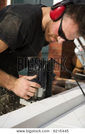 Carpenter Usiing A Router On A Newly Build Door Frame