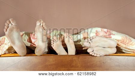 Tree pairs of legs of the happy family in bed - father, mother and child