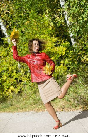 Young Woman With Leaves In Hands In Jump In Wood In Autumn