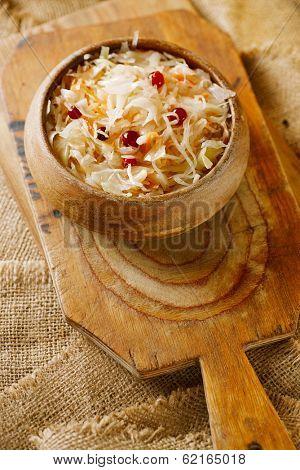 sauerkraut - Sour cabbage -  wooden bowl with crunberry