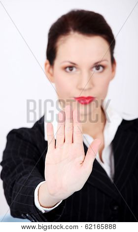 Beautiful business woman is keeping her hand ahead, making stop sign.
