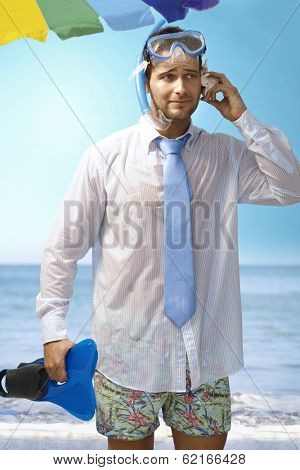 Young businessman using seashell as mobilephone on the beach wearing shirt and tie and scuba diving equipments.