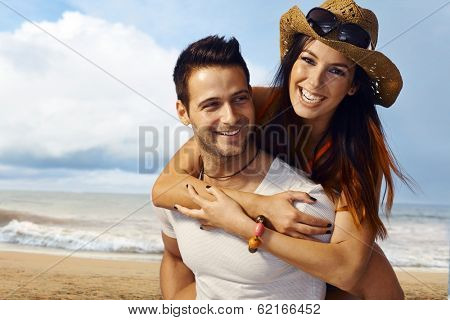 Happy loving couple having fun on the beach, enjoying summer holiday piggyback.