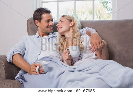 Relaxed loving young couple with coffee cups looking at each other in living room at home