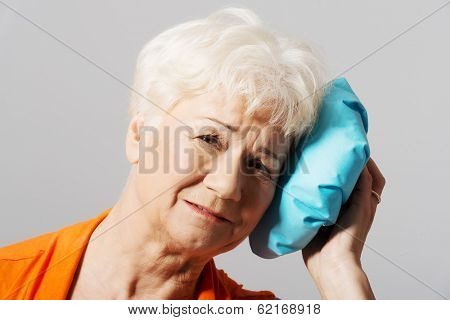 An old lady with ice bag by her head. Isolated on grey.