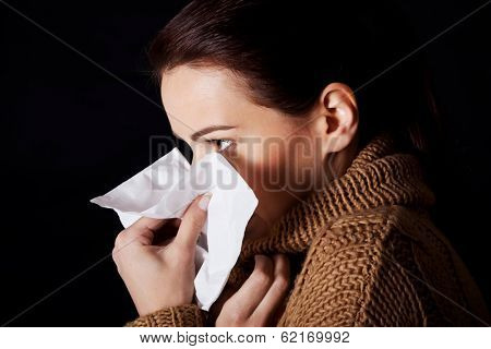 Sad young girl with tissue. Over black background.
