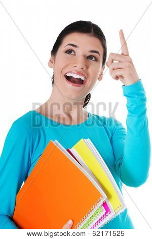 Young happy female student is pointing up and holding workbooks. Isolated on white.