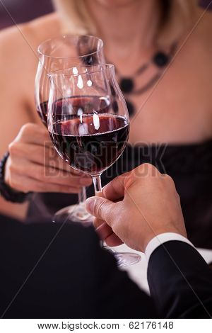 Close-up Of Couple Toasting Wine