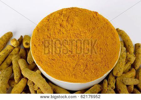 Turmeric powder in white bowl with turmeric sticks