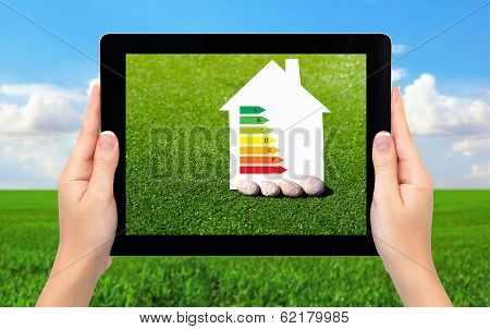 Female Hands Holding A Tablet With A House And Sign Energy Saving On A Background Of Field