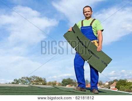 Worker Putting Bitumen Shingles On A Roof