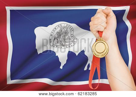 Medal In Hand With Flag On Background - State Of Wyoming. Part Of A Series.