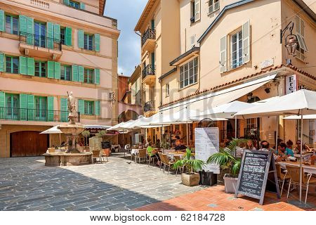 MONACO-VILLE, MONACO - JULY13, 2013: People having dinner in outdoor restaurant on small quiet square surrounded by houses in Monaco-Ville, Monaco  - popular touristic resort and place to visit.