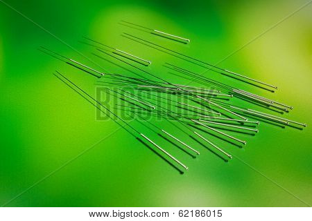 Needles for acupuncture on green background