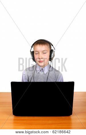 Kid In Headphones Behind Laptop