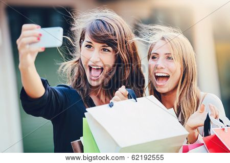 Beautiful girls with shopping bags taking a