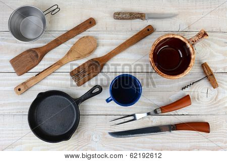 High angle shot of assorted kitchen and camping utensils. Items include: pan, bowl, cup, knife, fork, cork screw. Horizontal format.