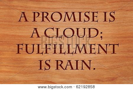 A promise is a cloud; fulfillment is rain - an Arabian Proverb, on wooden red oak background