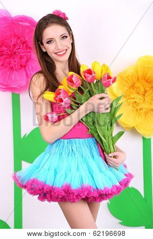 Beautiful young woman in petty skirt with bouquet of tulips on decorative background