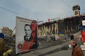 KIEV, UKRAINE - Mar 24, 2014: Stephan Bandera poster (Ukrainian nationalist icon ) near Burnt down t