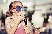 foto of candy cotton  - Teenage girl eating cotton candy outdoor - JPG