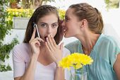 Young woman whispering secret into a friends ear while shes on call at cafe