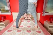 Couple in an embrace stand upside down on the bed in bedroom
