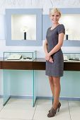 picture of jewel-case  - Shop assistant stands near the window case at jeweler - JPG