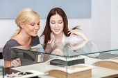 stock photo of jewel-case  - Two girls looking at glass case with jewelry at jeweler - JPG