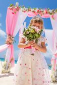 image of cabana  - young happy kid girl in beautiful dress on tropical wedding setup background - JPG