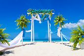 foto of cabana  - wedding arch decorated with flowers on tropical sand beach - JPG