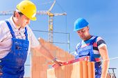 foto of bricklayer  - construction site worker or bricklayer with helmets controlling walls with a bubble level or building or laying or bricklaying wall on building - JPG